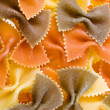 Tricolour dry pasta farfalle background - Stock Photo