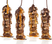 Tower of Chocolate caramel syrup poured on chocolate pieces,nuts, cookies — Stock Photo