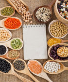 Mix from different beans, legumes, peas, lentils in spoon on the sackcloth background — Stock Photo