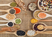 Various food ingredients: beans, legumes, peas, lentils in wooden spoon on the sackcloth background — Stock fotografie