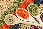Lentils, beans, peas, soybeans, legumes with spoons textured background — Stock Photo