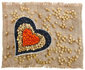 Different types of grains of lentils in the form of heart on red canvas background — Stock Photo