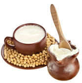 Powdered milk drink in clay pitcher and cup on white background — Stock Photo