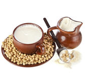 Powdered milk drink in clay pitcher and cup, spoon, soy beans, on white background — Stock Photo