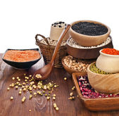 Verschillende soorten bonen zaden, linzen, erwten in schotel op houten bureau — Stockfoto