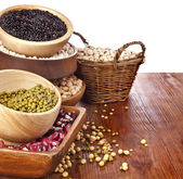 Different kinds of bean seeds, lentil, peas in dish on wooden desk — Stock Photo