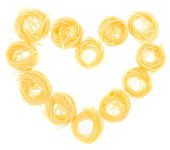 Nest pasta packed in a heart isolated on a white background — Stock Photo