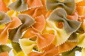 Tricolour dry pasta farfalle background — Stock Photo