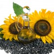 Sunflowers seeds and glass bottle oil — Stock Photo #14127859