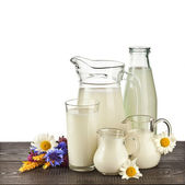 Glass and jar of milk on the wooden table isolated on white background — Stock Photo