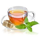 Chá em copo de vidro com folha de hortelã e cubos de açúcar de cana-de-marrom isolados em um fundo branco — Foto Stock