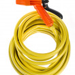 Yellow garden hose coiled with spray nozzle - Stock Photo