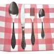 Antique silverware, fork, knife and spoon on the kitchen dining napkin in a cell - Stock Photo