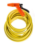 Yellow garden hose coiled with spray nozzle — Stock Photo
