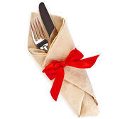 Cutlery and napkin with red ribbon bow isolated on white — Stock Photo