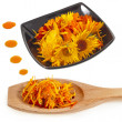 herbal calendula in black bowl and wooden spoon isolated white background — Stock Photo