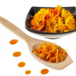 Royalty-Free Stock Photo: Herbal calendula in black bowl and wooden spoon Isolated white background