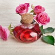 Rose oil in bottle with flowers - Stock Photo