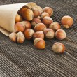 Filbert nut in paper bag on texture surface of old wood — Stock Photo