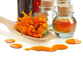 Herbal calendula in the glass and aromatherapy essential oil Isolated white background — Stock Photo