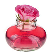 Rose oil in bottle with flower isolated on white — Stock Photo