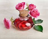 Rose oil in bottle with flowers — Stock Photo