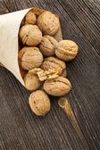 Walnut nut in paper bag on texture surface of old wood background — Stock Photo