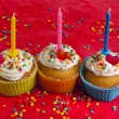 Birthday cupcakes with colorful sprinkles on red background — Stock Photo