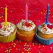 Birthday cupcakes with colorful sprinkles on red background - Stok fotoğraf