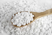 Wooden spoon full of white granular culinary sugar — Stock Photo