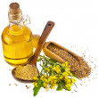 Mustard oil jar and mustard powder spoon, seeds scoop, with fresh mustard flower on white - Stock Photo