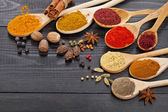 Powder spices on spoons in wooden background — Stock Photo