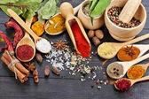 Blanda aromatiska kryddor på skedar i svart trä bakgrund — Stockfoto
