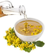 Mustard oil pour in a bowl with mustard flower bloom isolated on white — Stock Photo