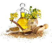 Mustard oil jar and mustard powder spoon, seeds scoop, with fresh mustard flower on white — Photo