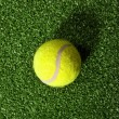 Tennis ball against fake grass background - Stock Photo