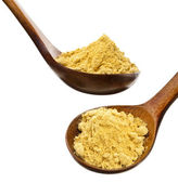 Mustard powder in a wooden spoon isolated over white — Stok fotoğraf