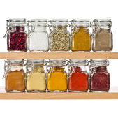 Powder spices in glass bottle jar on a wooden shelf on white — Stock Photo