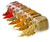 Pulver färgstarka kryddor i glasburk på vit — Stockfoto