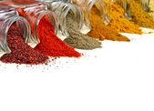 De kleurrijke kruiden poeder in glazen pot op wit — Stockfoto