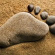 Alone trace footprint of the feet made of a pebble stone on sea sand texture background — Stock Photo #14867821