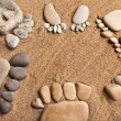 Trace feet family of a pebble stone on the sea sand backdrop — Stock Photo