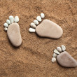 Stock Photo: Trace bare feet walking made of pebble stones on beach sand background