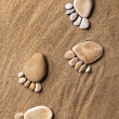Trace feet steps of a pebble stone walking on the sea sand backdrop — Stock Photo #14867835