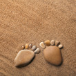 Two trace feet made of a pebble stone on the sea sand desert — Stock Photo #14867851