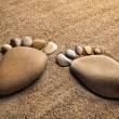 Pair trace feet made of a pebble stone on the sea sand desert texture backdrop — Stock Photo #14867857