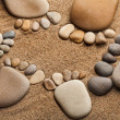 Trace feet of a pebble stone on the sea sand backdrop — Stock Photo #14867873