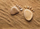 Two trace feet made of a pebble stone on the sea sand desert — Stock Photo