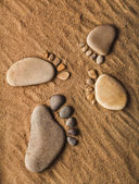 Trace feet steps of a pebble stone walking on the sea sand backdrop — Photo
