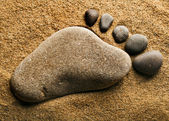 Alone trace footprint of the feet made of a pebble stone on sea sand texture background — Stock Photo